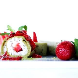 Maki sucré avec une crêpe au thé matcha, fraises et coulis de fruits rouges