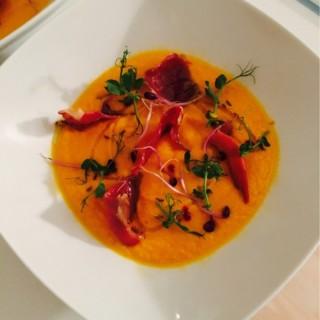 Velouté de carotte émulsion à l'huile d'olive et cumin, effeuillé de jambon artisanal