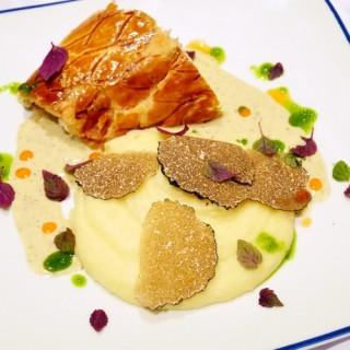 Bar de ligne en croute feuilletée, écrasé de pommes de terre, copeaux de truffe, fumet de crustacés au basilic et à l'aneth, feuilles de shizo et huile de homard