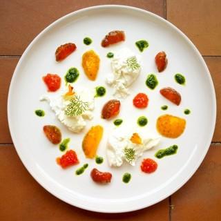 Cœurs des tomates, burrata, vinaigrette au mezcal et herbes.